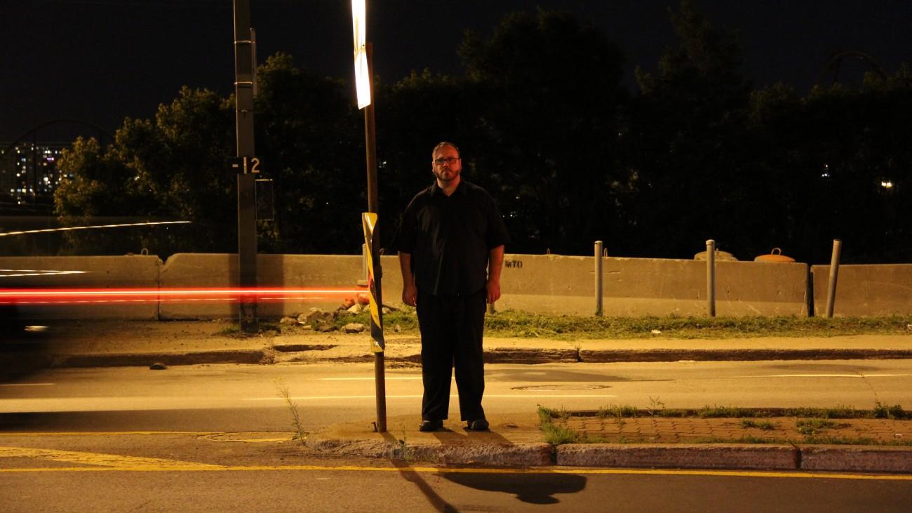 Steve Giasson. Performance invisible n° 3 (Demeurer immobile et en silence (un certain temps).) Performeur : Steve Giasson. Participant involontaire : Inspecteur de police. Crédit photographique : Daniel Roy. 17 juin 2015.
