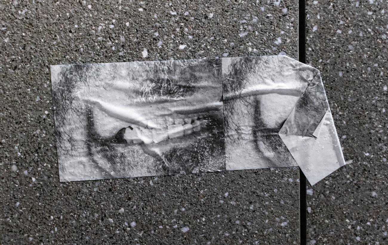 Steve Giasson. Performance invisible n° 144 (Feindre un sourire). D'après Steve Giasson. Performance invisible n° 33 (:) → :( (ou Rappeler la ruine d'un sourire)). D'après Grupa šestorice autora [Group of Six Artists]. Distributing photos of a model's smile from Burda Magazine for women and gluing them on the pavement at the tram stop during the exhibition - action of the Group of Six Artists at the former Republic Square, Zagreb, 1975.Performeur : Steve Giasson. Crédit photographique : Steve Giasson (avec l'assistance de Martin Vinette). Place des Arts, Montréal, 25-28 octobre 2019.