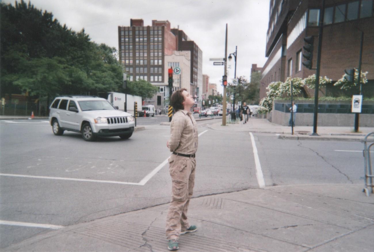 Steve Giasson. Performance invisible n° 5 (Adopter, pendant un certain temps, au coin d'une rue, la position de Marie van Goethem par Edgar Degas et demeurer debout dans une attitude de repos, les jambes en dehors, les pieds formant la quatrième position classique du ballet, les mains derrière le dos, le buste dressé et la tête rejetée en arrière). Performeur :Jean-Philippe Luckhurst-Cartier. Performance activée dans le cadre de Parcours Neuf à Cinq, Occurrences estivales 2015, Péristyle nomade. Montréal. 13 août 2015.
