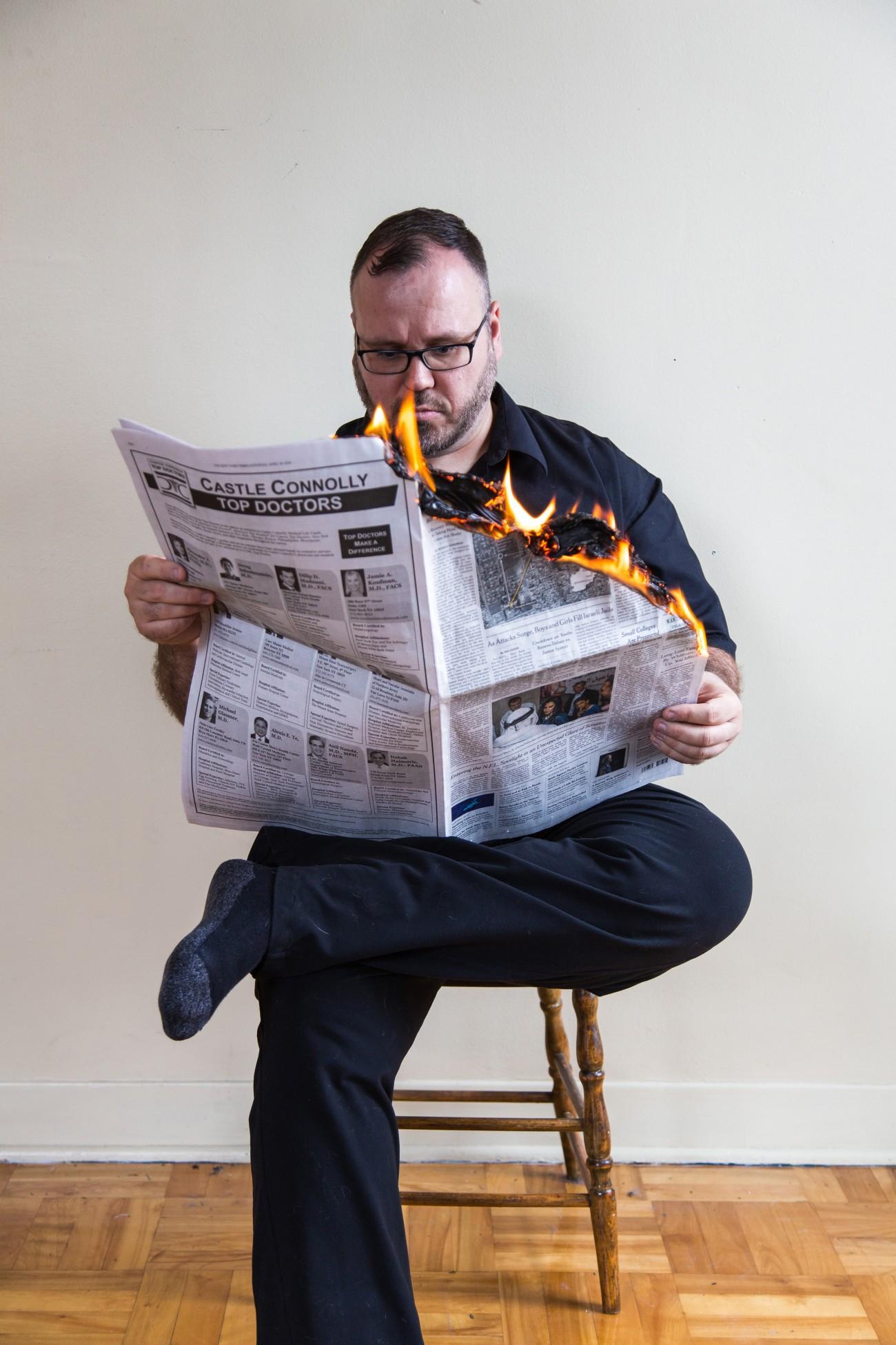 Steve Giasson. Performance invisible n° 110 (Faire de la rétention d'information). Reenactment de EndreTót. I am reading a burning newspaper / Égő újságot olvasok. 1972/74. Performeur : Steve Giasson. Crédit photographique : Daniel Roy. 1er mai 2016.