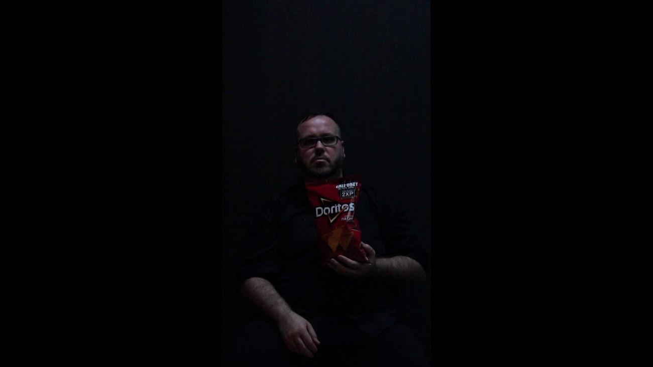 Steve Giasson. Performance invisible n° 51 (Manger un sac familial de Doritos en 10 minutes). Performeur : Steve Giasson. Crédit photographique : Daniel Roy. 30 novembre 2015.